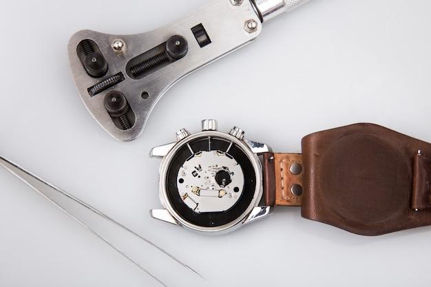 Mecanismo de reloj de pulsera y herramientas de reparación aisladas en blanco