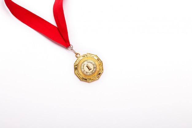 Medalla de oro con cinta roja sobre fondo blanco