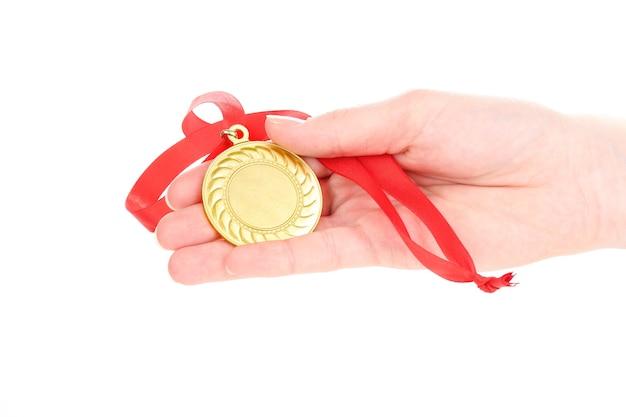 Medalla de oro en mano sobre blanco