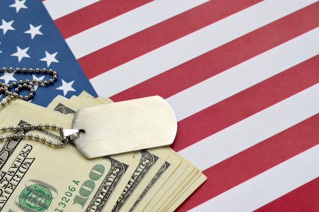 Medallones de identificación del ejército y billetes de dólar en la bandera de estados unidos. pensión militar, salario en el ejército o seguro militar