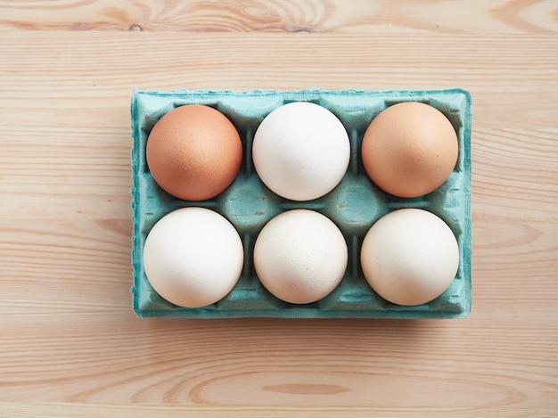 Media docena de huevos crudos frescos de color marrón y blanco en una caja de cartón verde colocada sobre una mesa de madera
