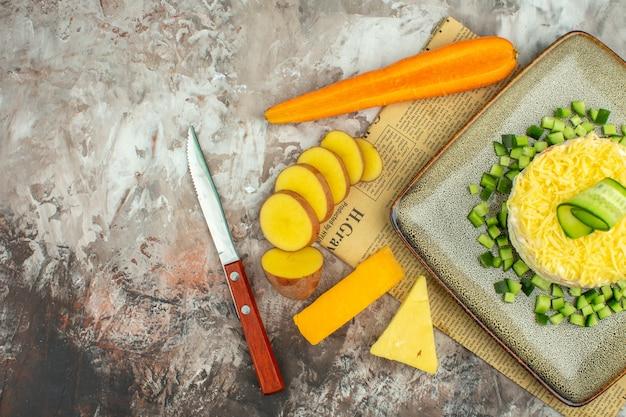 Media foto de deliciosa ensalada en un periódico viejo y dos tipos de queso y zanahorias, patatas picadas en una mesa de colores mezclados