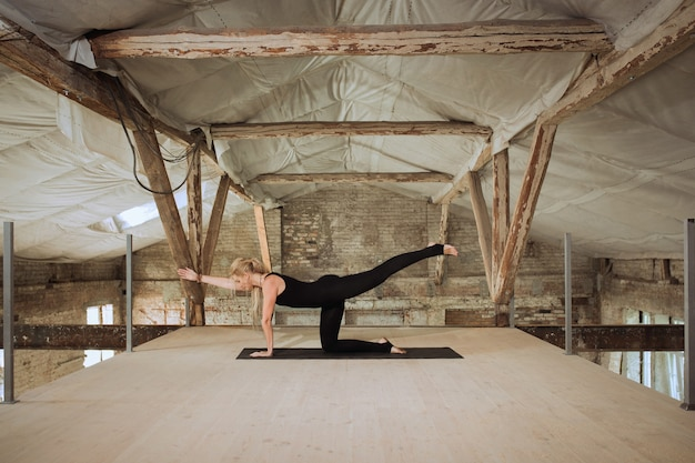 Media luna. una joven atlética ejercita yoga en un edificio de construcción abandonado. equilibrio de salud mental y física. concepto de estilo de vida saludable, deporte, actividad, pérdida de peso, concentración.