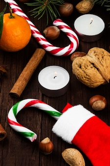 Media, velas, abeto, mandarinas, bastón de caramelo, canela, almendras y avellanas sobre una superficie de madera oscura.