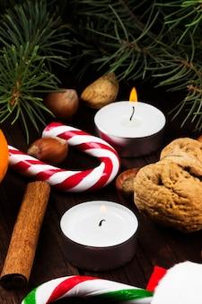 Media, velas, abeto, mandarinas, bastón de caramelo, canela y avellana sobre una superficie de madera oscura.
