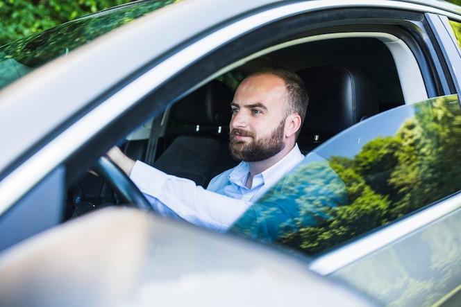 Mediados de hombre adulto que se sienta dentro del coche