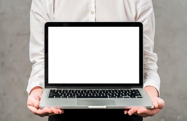Mediados de sección de una empresaria joven que sostiene el ordenador portátil en la mano que muestra la pantalla en blanco