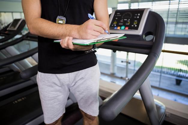 Mediados de sección del hombre en la cinta de correr escribiendo en el portapapeles en el gimnasio
