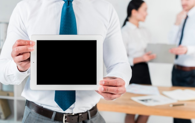 Mediados de sección de un hombre de negocios que muestra la tableta digital de la pantalla en blanco en el lugar de trabajo