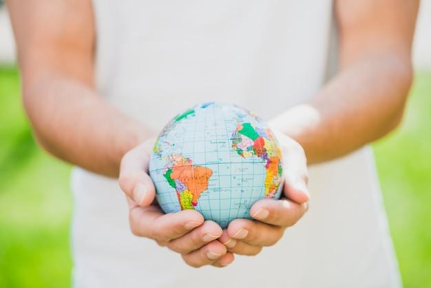 Mediados de sección del hombre que sostiene el pequeño globo en la mano
