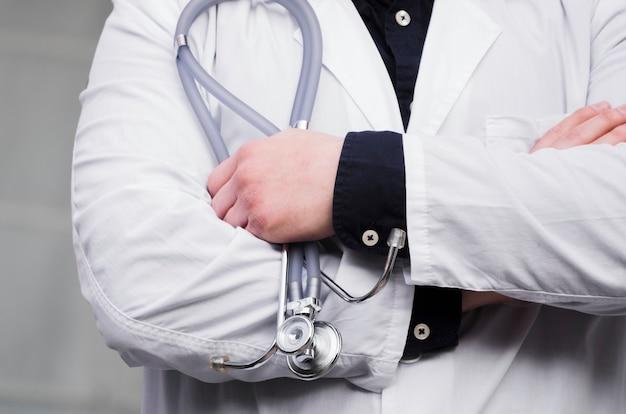 Mediados de sección de la mano del doctor de sexo masculino que sostiene el estetoscopio en la mano