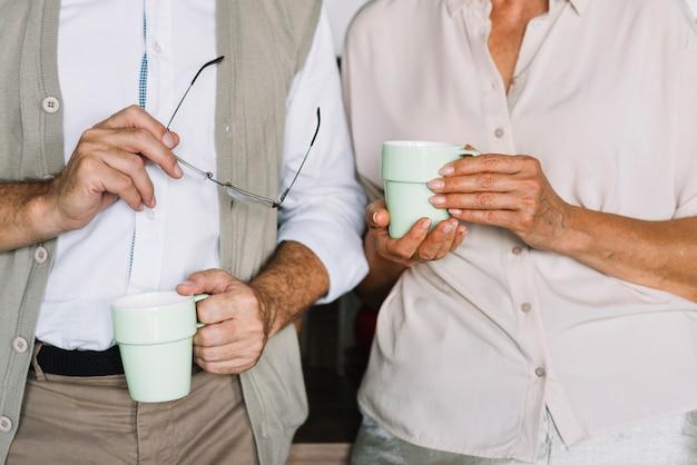 Mediados de sección de una pareja de ancianos sosteniendo la taza de café en la mano