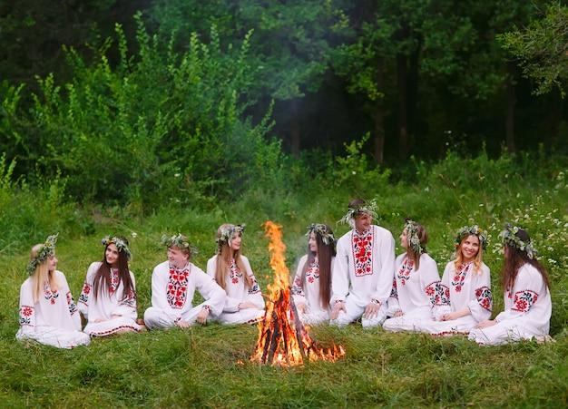 A mediados del verano, jóvenes con ropa eslava sentados en el bosque cerca del fuego.