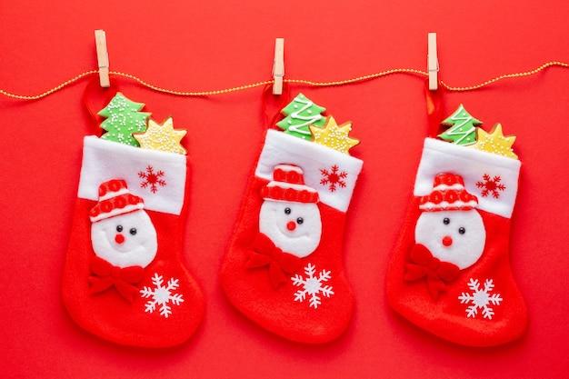 Medias de navidad llenas de pan de jengibre con glaseado sobre fondo rojo.