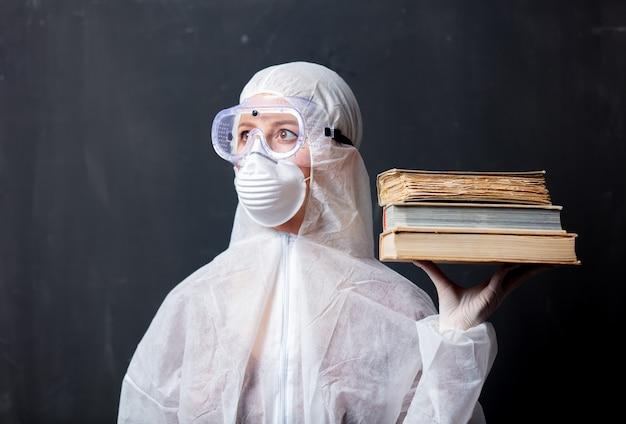 Medic mujer vestida con ropa protectora contra el virus con libros