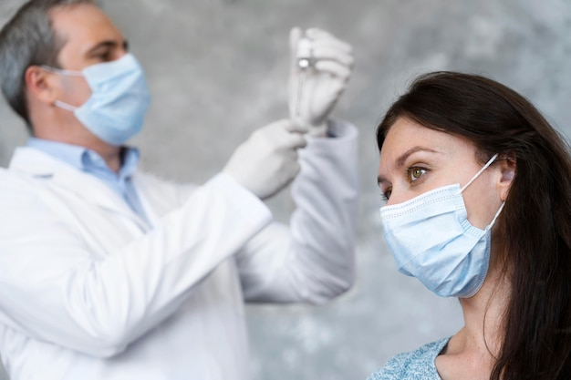 Medic preparando la vacuna para el paciente femenino