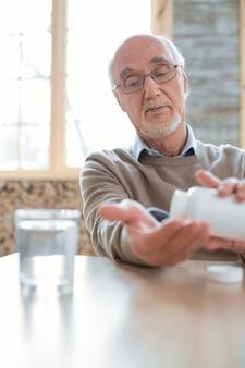 Medicación para la presión arterial. hombre mayor agradable hermoso que se sienta en el fondo borroso mientras que coloca las píldoras en la mano y que mira hacia abajo