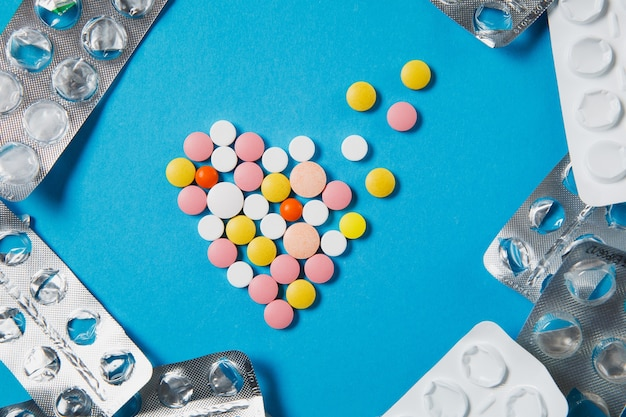 Medicamentos coloridos comprimidos redondos en forma de corazón de difusión aislado sobre fondo azul.