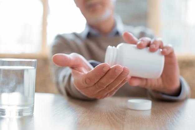 Medicamentos para el corazón. cerca de atractivas manos masculinas senior llevando una botella llena de medicación