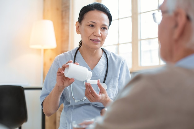 Medicamentos esenciales. doctor agradable atractivo que eleva la botella llena de pastillas mientras mira al hombre mayor