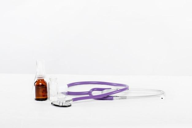 Medicamentos y un estetoscopio están sobre la mesa del hospital