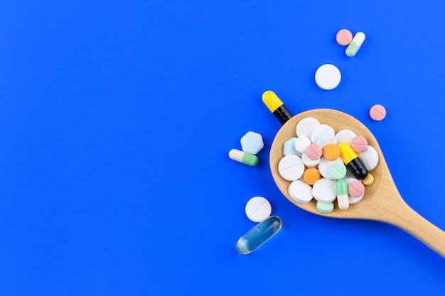 Medicamentos, pastillas, medicamentos, cápsulas, aceite de pescado en una cuchara aislada