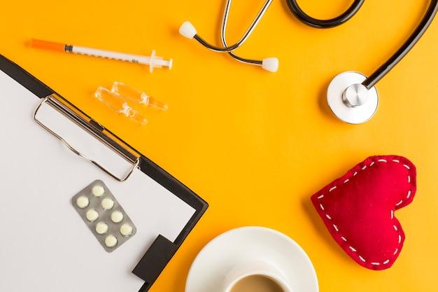 Medicamentos sobre portapapeles con corazón cosido; ampolla; estetoscopio y taza de café; inyección sobre fondo amarillo