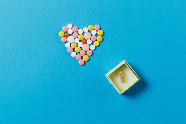 Medicamentos, tabletas redondas de colores blancos en forma de corazón aislado sobre fondo azul.
