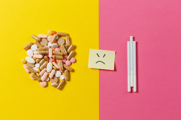 Medicamentos, tabletas redondas de colores blancos, píldoras dispuestas abstractas tres cigarrillos sobre fondo de color amarillo