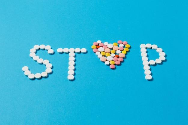 Medicamentos, tabletas redondas de colores blancos en word stop aislado sobre fondo azul. Foto gratis