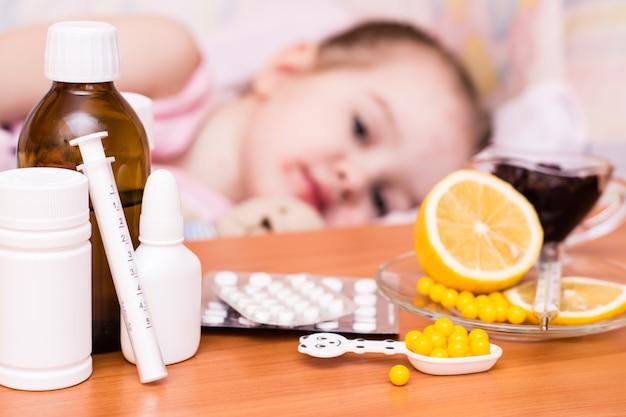 Medicamentos y vitaminas en la mesa del niño en una cama que tiene varicela