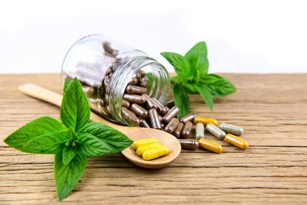 Medicina alternativa a base de hierbas en cápsulas en mesa de madera.