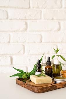 Medicina alternativa, cosmética natural. el aceite de cbd y el cannabis deja la vista frontal de los cosméticos, espacio de copia, diseño de maqueta