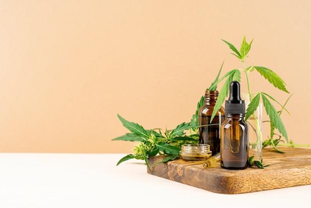 Medicina alternativa, cosmética natural. el aceite de cbd y el cannabis deja la vista frontal de los cosméticos sobre fondo naranja, espacio de copia