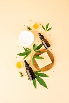 Medicina alternativa, cosmética natural. vista superior de cosméticos de hojas de cannabis y aceite de cbd sobre fondo naranja, endecha plana