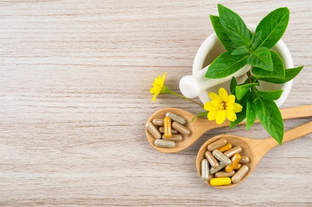 Medicina alternativa, vitaminas y suplementos naturales sobre madera.