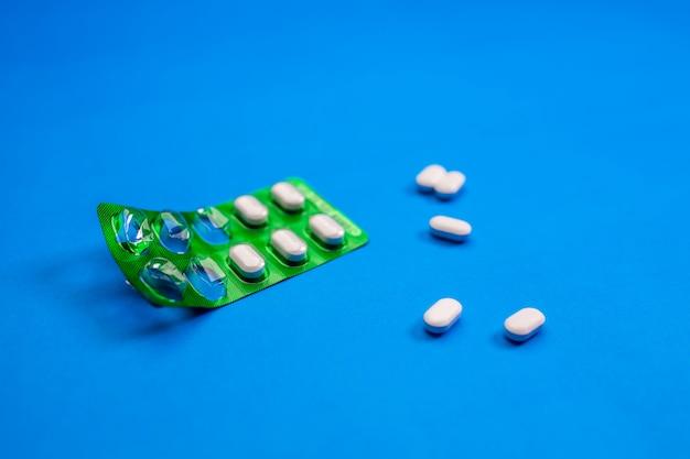 Medicina en el blister verde que miente en un azul. salud.