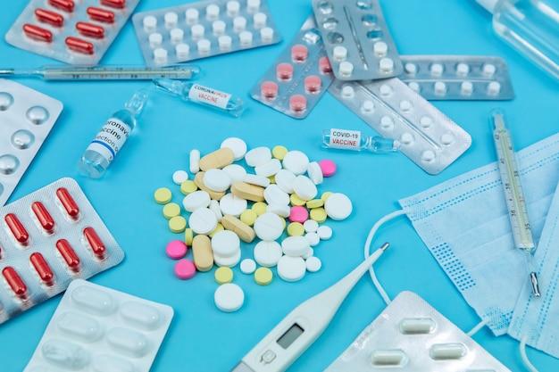 Medicina para el coronavirus. medicamentos en la lucha contra covid-19. píldoras, jeringas, termómetro, máscara médica sobre una mesa azul. .