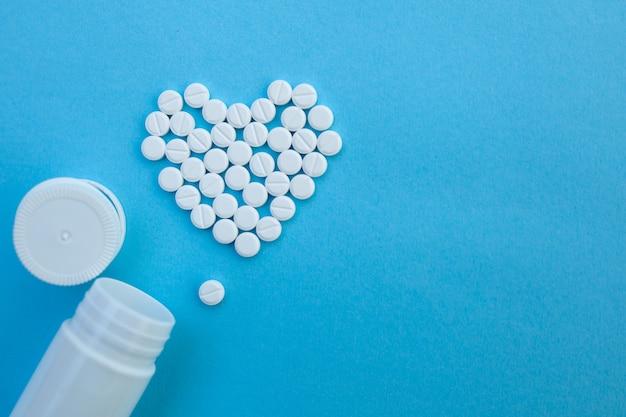 Medicina, cuidado de la salud y concepto de farmacia - píldoras y medicamentos en forma de corazón.