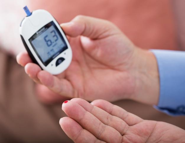 Medicina, diabetes, glucemia, cuidado de la salud y concepto de personas: cerca del dedo masculino con la tira de prueba
