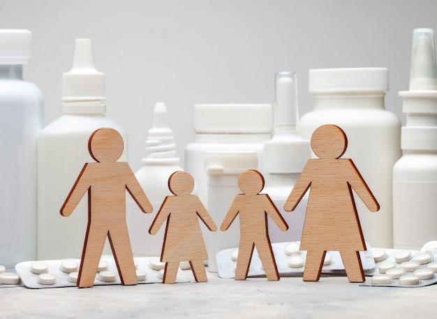 Medicina familiar. papá, mamá, hija e hijo se dan la mano sobre el fondo de los medicamentos.