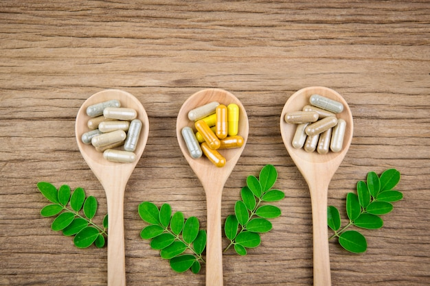 Medicina herbaria alternativa, vitaminas y suplementos naturales sobre fondo woodden
