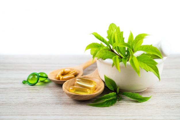 Medicina herbaria de hierba de hoja verde, cápsula y vitamina en mesa de madera