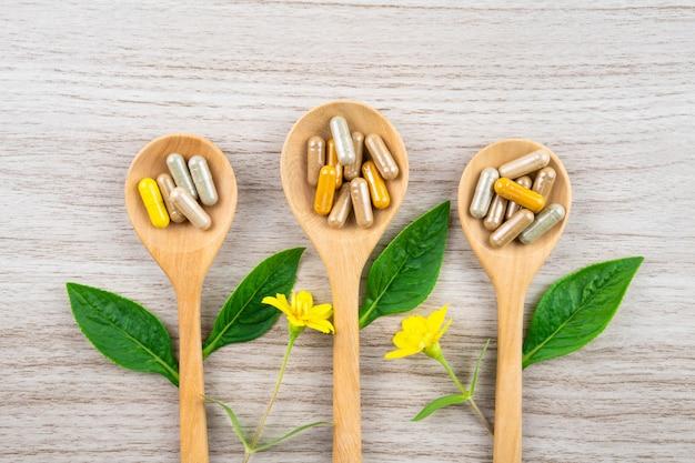 Medicina herbaria de hierba de hoja verde, píldora, tableta, cápsula, droga y vitamina en cuchara de madera