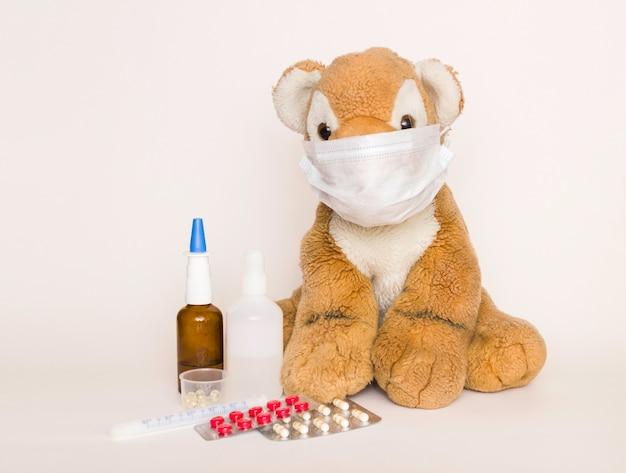 Medicina infantil tigre de juguete suave para niños en una máscara médica desechable sobre un fondo blanco.