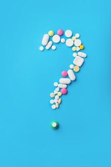 Medicina pastillas, tabletas y cápsulas sobre fondo azul.