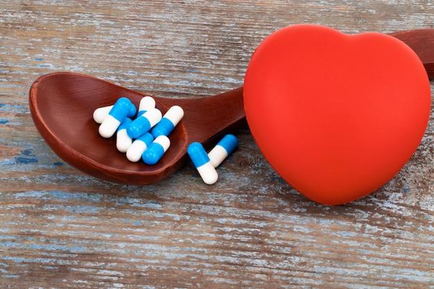 Medicina píldoras, tabletas y cápsulas en cuchara de madera con corazón.