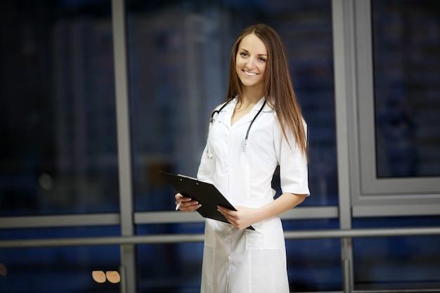 Medicina retrato de primer plano en la cabeza de una mujer amable, alegre, sonriente y confiada, profesional de la salud en uniforme azul.