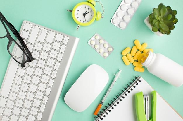 Medicinas; papelería; dispositivos inalámbricos y despertador sobre fondo verde