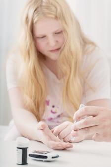Medición del nivel de azúcar en sangre de una niña adolescente con glucómetro